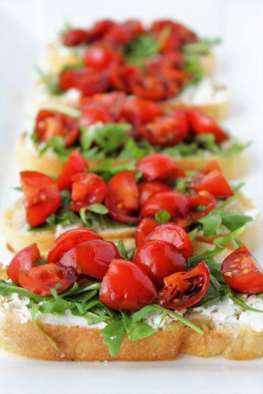bread with goat cheese spread arugula tomatoes and balsamic on a platter