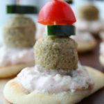 mini naan bread, topped with yogurt sauce, meatball, cucumber, tomato on a toothpick