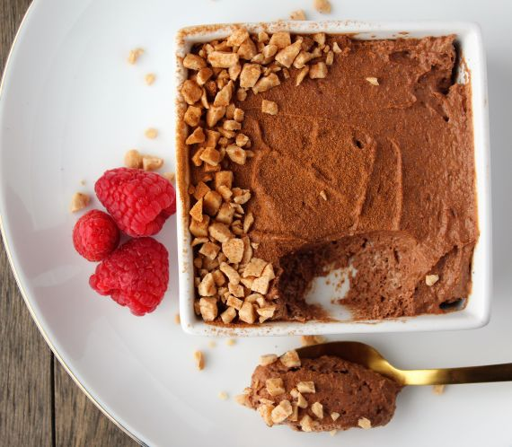 white square bowl filled with chocolate mousse and toffee bits garnished with fresh raspberries