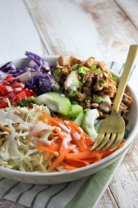 chicken and veggies in a bowl with dressing and fork