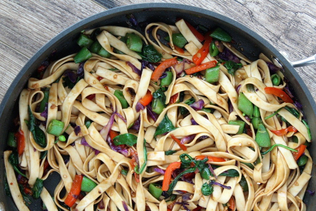 large skillet with sauced lo mein noodles and veggies