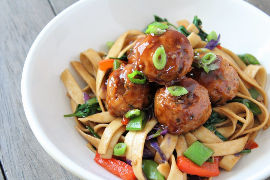 white bowl lo mein noodles and veggies with hoisin glazed meatballs with wood backdrop