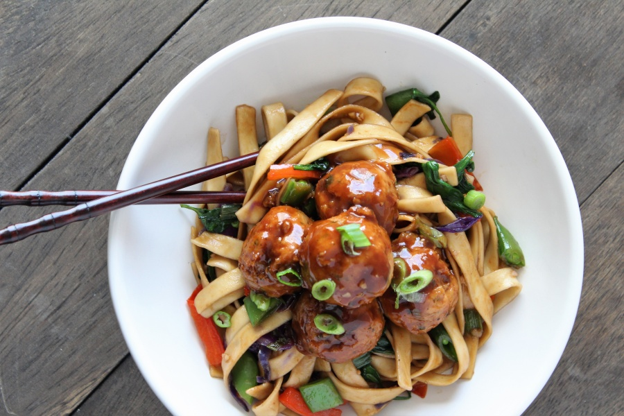white bowl chop sticks lo mein noodles and veggies with hoisin glazed meatballs with wood backdrop