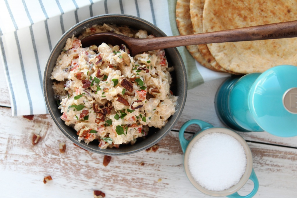 grey bowl with chicken salad and spoon pita bread and salt and pepper in background
