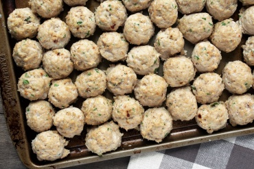 baking sheet pan with baked chicken meatballs laying on wood backdrop and towel.