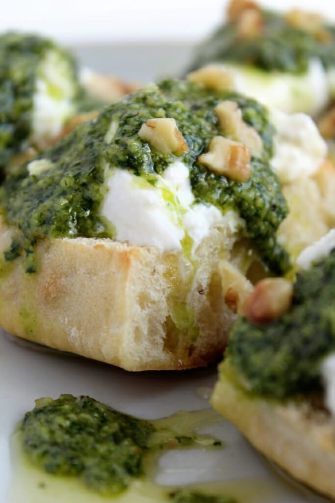 square bread on round plate topped with white cheese, honey, olive oil, fresh basil pesto and walnuts.