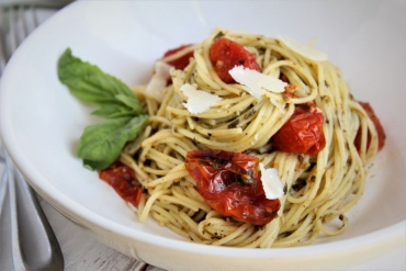 pasta in white bowl with basil, cherry tomatoes, parm and pesto sauce
